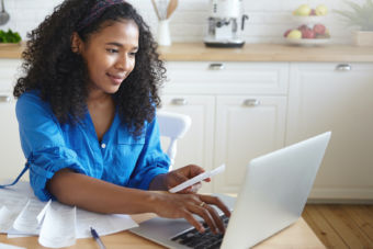 Candid shot of focused beautiful young African housewife wearing headband and casual shirt paying utility bills online using laptop computer, sitting at kitchen table with papers and smiling