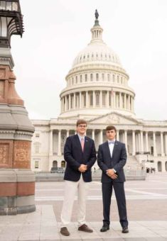Two young boys in suits, standing in front of the Capitol Building