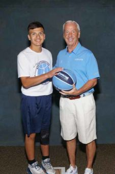 Young man placing his hand on a basketball held by Roy Williams beside him