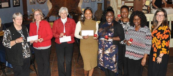 Group of women smiling, holding checks