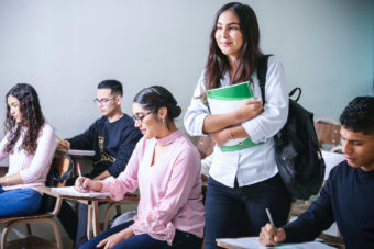 Girl in classroom holding a notebook, with other students sitting at desks