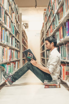 Man sitting on floor of library reading a book