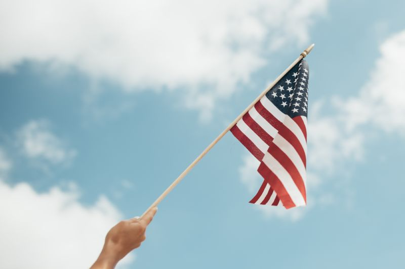 Hand holding an American flag in the air